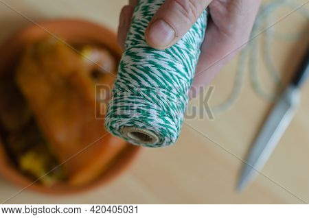 A Hand Holds A White And Green Skein Of Twine Over The Kitchen Table. A Clay Plate With Marinated Me