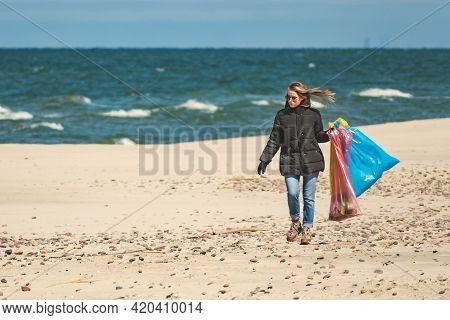 Nida, Lithuania - May 8 2021: Beautiful Volunteer Girl Collecting Plastic Trash Rubbish Garbage On T