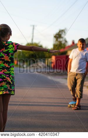 Defocus Happy Young Girl And Boy Playing On Skateboard In The Street. She Put Arms Out To The Sides