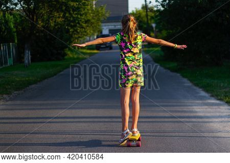 Defocus Happy Young Girl Playing On Skateboard In The Street. She Put Arms Out To The Sides. Caucasi
