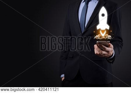 Startup Business Concept, Businessman Holding Tablet And Icon Rocket Is Launching And Soar Flying Ou
