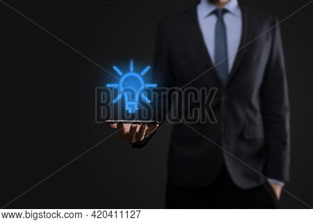 Businessman In A Suit With A Light Bulb In His Hands. Holds A Glowing Idea Icon In His Hand. With A