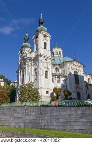 White Catholic Church Of St. Maria Magdalena In Karlovy Vary, Czechia. Sunny Day, Blue Sky. Low Angl
