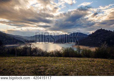 Sunset in mountain landscape. Mountain lake in sunset. Sunset on mountain lake landscape. Meadow and mountains landscape. Blue mountains and last sun lights landscape. Sunset in mountain forest. Landscape. Mountains. Sunset.