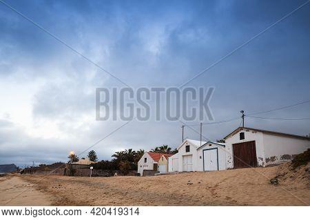 Coastal Barns On The Beach Of The Island Of Porto Santo Under Cloudy Blue Sky In The Morning. Madeir