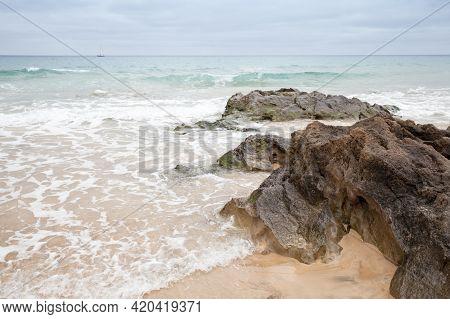 Wet Coastal Rocks On A Cloudy Day. Beach Of Porto Santo Island, Madeira Archipelago, Portugal