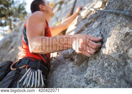 Climber In Red T-shirt Climbs A Gray Rock. A Strong Hand Grabbed The Lead, Selective Focus. Strength