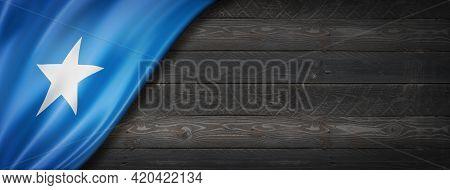Somalia Flag On Black Wood Wall. Horizontal Panoramic Banner. 3d Illustration