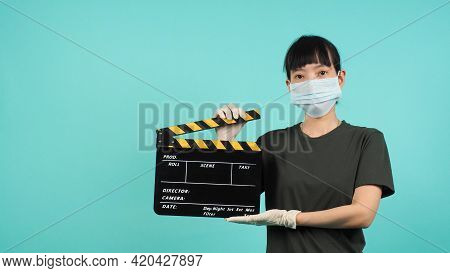 Black And Yellow Clapper Board Or Movie Slate.asian Woman Wear Face Mask And Hand Wear Medical Glove