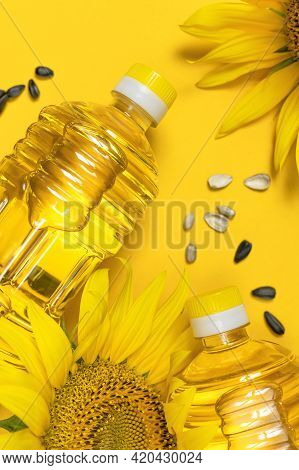 Plastic Bottles With Sunflower Oil, Fresh Yellow Sunflowers, Sunflower Seeds On Yellow Background. F