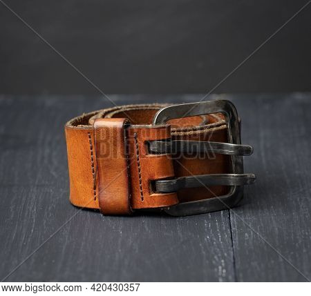 Brown Leather Men's Belt With Metal Buckle On A Wooden Background, Close Up