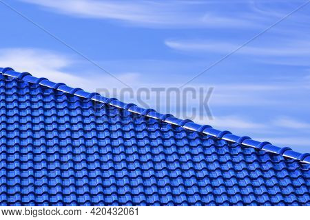 Part Of Glossy Blue Ceramic Roof Tiles Against White Cloud And Blue Sky In Diagonal View