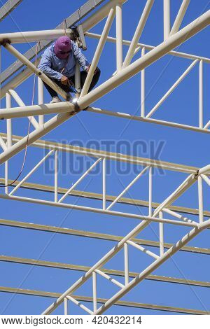 Low Angle View Of Asian Construction Worker Is Welding Metal On Roof Building Structure Against Blue
