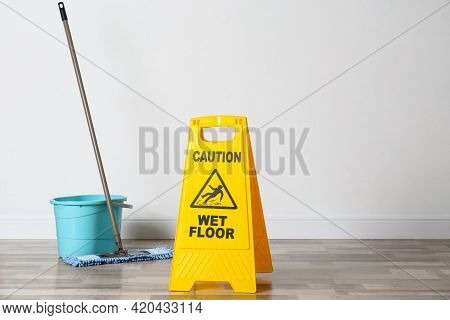 Safety Sign With Phrase Caution Wet Floor, Mop And Bucket Indoors. Cleaning Service