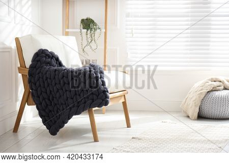 Knitted Merino Wool Plaid On Armchair In Room. Space For Text