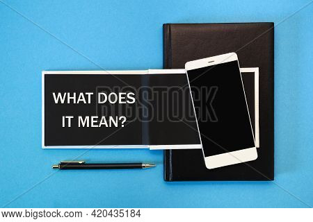 A White Notebook With Black Pages, A Smartphone And A Pen On A Blue Background. The Inscription What