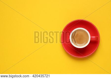 Aromatic Coffee In Red Cup On Yellow Background, Top View. Space For Text