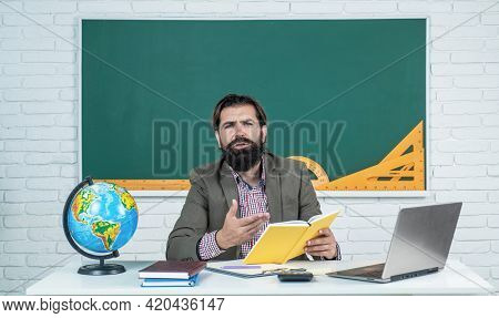 Informal Education. Male Student Sit In School Classroom On Lesson With Blackboard. Pass The Exam. L