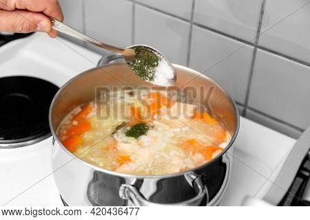 The Chef Cooks Finnish Salmon Soup. The Cook Puts The Spice Into A Saucepan.