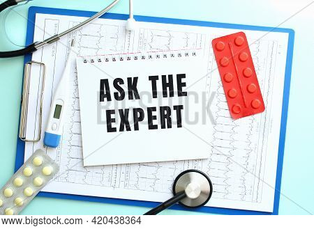 A Notepad With The Text Ask The Expert Lies On A Blue Medical Clipboard With A Stethoscope And Pills