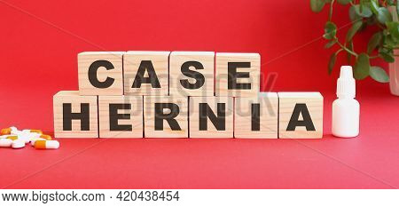 The Words Case Hernia Is Made Of Wooden Cubes On A Red Background With Medical Drugs.