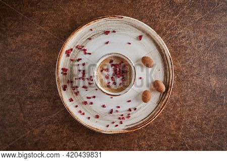 Top View Coffee With Sublimated Raspberries In Light Mug. Nearby Candy In Chocolate. Copy Space