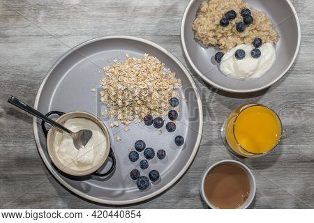 Healthy Breakfast Flat Lay Image. Porridge Oats With Blueberries Fruit And Yoghurt With Tea And Oran