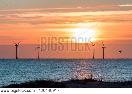 Tropical Island Sunset With Offshore Wind Farm Turbines On Ocean Horizon. Beautiful Sunrise Or Sunse