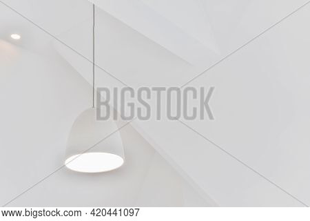 Low Angle Of Loft Style Lamp Hanging Under White Geometric Ceiling Of Attic Apartment With Minimalis