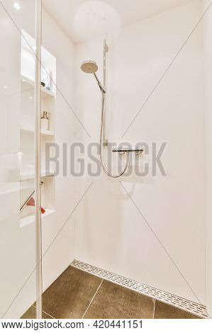 Shower Faucet Hanging On White Tiled Wall In Light Washroom In Modern Flat