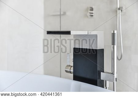 Minimalist Faucet Design With Wide Spout And Thin Shower Nozzle Above White Tub In Bathroom