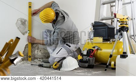 House Renovation Concept, Man Worker Looks At The Spirit Level Checks The Wall, Helmet And Safety He