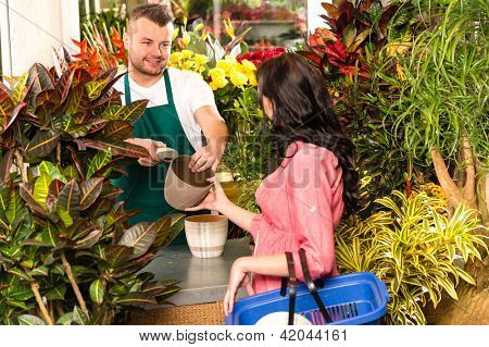 Man selling pot woman customer flower shop gardening plant