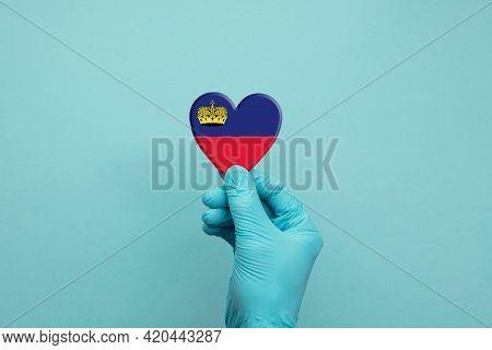 Hands Wearing Protective Surgical Gloves Holding Liechtenstein Flag Heart
