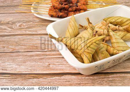 Ketupat Palas Or Rice Dumpling In A White Plate. Ketupat Palas Is A Natural Rice Casing Made From Yo