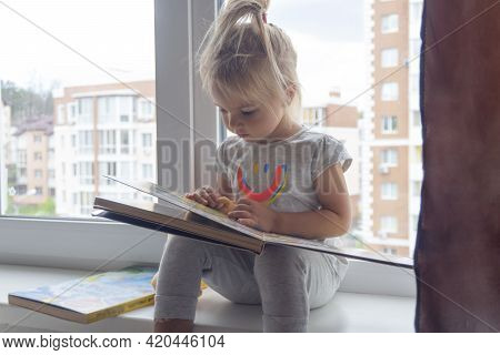 Cute Little Caucasian Child Sits Near Window And Reads Book, Busy Toddler, Calm Home Family Activity