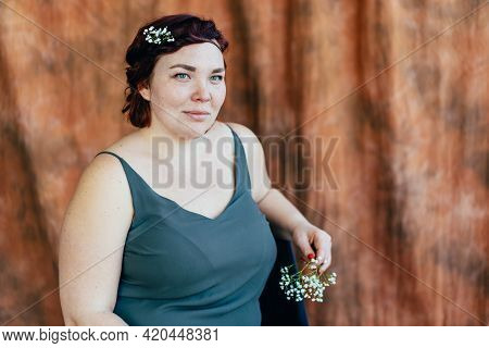 Full Beautiful Freckled Authentic Woman Looking At The Camera Sits In The Studio Against A Brown Wal