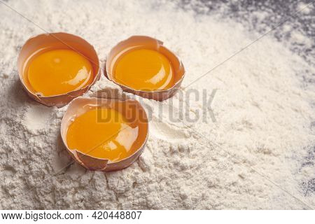 Dough, Baking And Cooking Background. Flour And Eggs On A Dark Wooden Kitchen Background As Ingredie