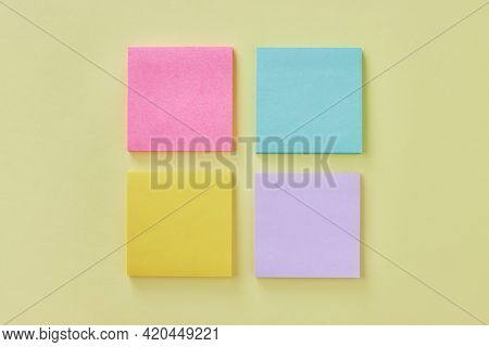 Top View Or Flat Lay 4 Color Stick Note Or Note Pad As Pink,green,yellow,purple On Modern Clean Offi