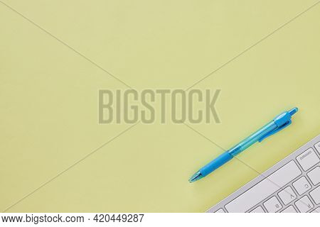 Top View Or Flat Lay Modern Office Desk Or Office Table With Computer Keyboard And Blue Pen. Yellow