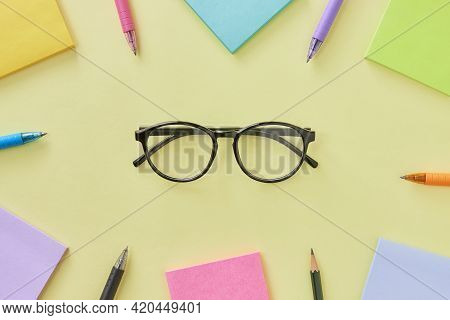 Top View Or Flat Lay Glasses And Stick Note And Pen On Office Desk Or Table Background. Office Suppl