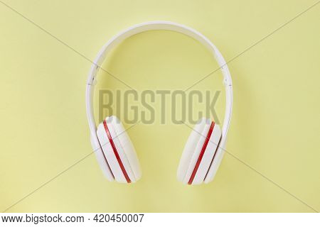 Top View Or Flat Lay White Headphone On Pastel Yellow Minimalist Background