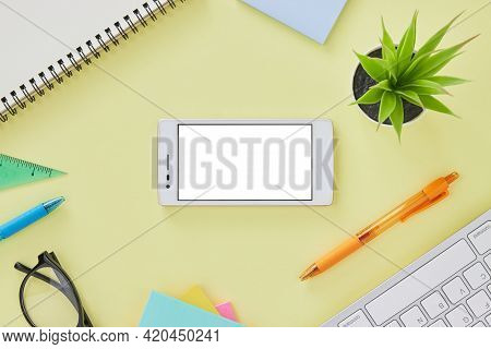 Horizontal Mobile Phone Or Smart Phone Mock Up On Office Desk Or Office Table With Office Supplies A