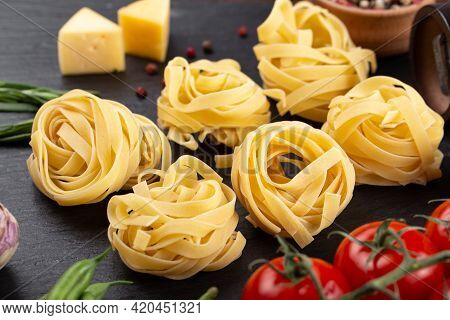 Raw Pasta Tagliatelle With Fresh Tomatoes, Peppers, Mushrooms,asparagus Beans, Spices And Cheese On
