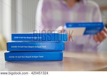 Close Up Of Woman At Home Reading Instructions On Supply Of Covid-19 Rapid Antigen Self-testing Kits