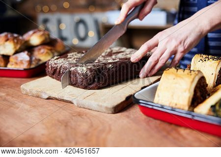 Sales Assistant In Bakery Cutting Freshly Baked Baked Brownies On Counter