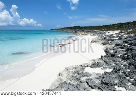 The Scenic View Of A Small Sandy Beach Surrounded By Sharp Rocks On Half Moon Cay Uninhabited Island