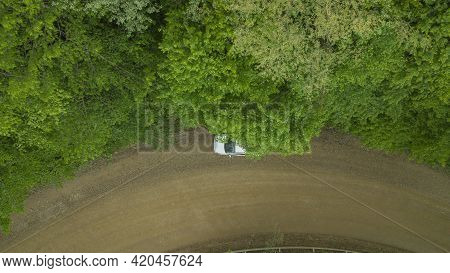 Aerial Top Down 4k View Of White Car Driving On Rural Road In Forest. Cinematic Drone Shot Flying Ov