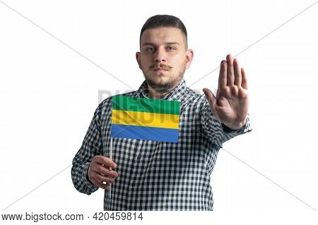 White Guy Holding A Flag Of Gabon And With A Serious Face Shows A Hand Stop Sign Isolated On A White