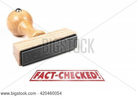 Wooden Rubber Stamp And Imprint With Text Fact-checked On White Background